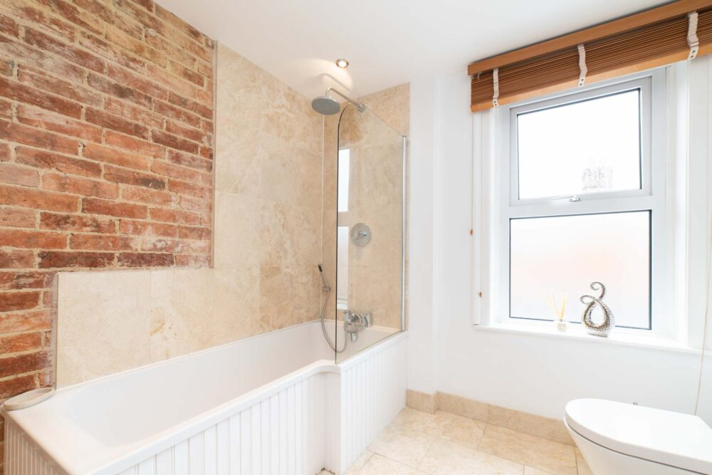 Bathroom with white and exposed brick walls